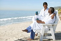 Couple in bathrobes relaxing on beach (thumbnail)