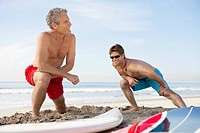Two male surfers stretching on beach