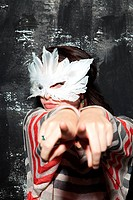 Woman wearing mask at party, pointing at camera