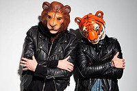 People wearing lion and tiger masks at party