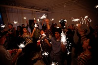 People dancing at party with sparklers