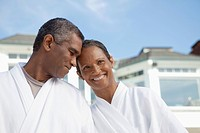 Smiling couple in bathrobes outdoors