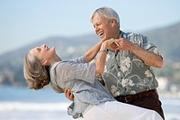 Happy senior couple dancing on beach