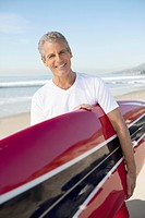 Portrait of smiling man carrying surfboard on beach