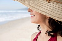 Close_up of smiling woman wearing straw hat on beach