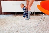 Mother helping baby son take first steps