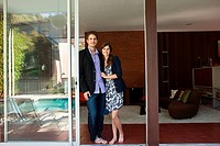 Couple standing by patio door, portrait