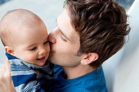 Father kissing baby son on cheek (thumbnail)
