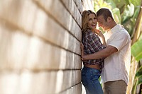 Couple leaning against wall and embracing