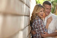 Midd adult couple embracing by wall
