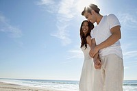 Couple dressed in white holding hands sandy beach