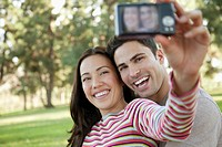 Young couple taking photograph of themselves in park (thumbnail)