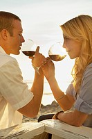 Young couple on beach drinking wine