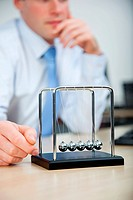 Office worker playing with newtons cradle