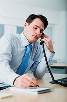 Office worker on telephone call, writing in notebook