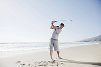 Man swinging golf club on beach