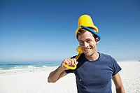 Happy mid adult man with wearing sand bucket on head, portrait (thumbnail)