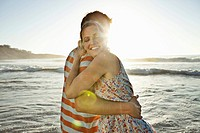 Happy couple embracing on beach, sea in background (thumbnail)