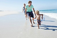 Parents with son 5_6 running on beach