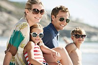 Happy family with son 5_6 and daughter 10_12 on beach and wearing sunglasses