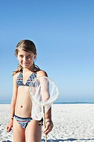 Portrait of girl 10_12 holding fishing net on beach