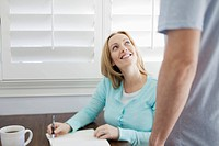 Woman doing notes while talking with man