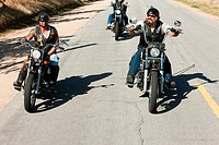 Three men riding motorcycles along desert road