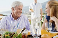 Young woman and senior man dining in outdoor restaurant