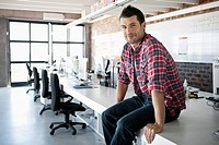 Portrait of smiling man sitting on desk in office (thumbnail)