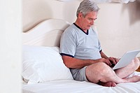 Senior man using laptop in bed