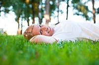 Smiling mature woman lying in grass