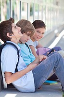 Three children sitting with earbuds and cell phone