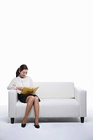 woman reads book on the sofa