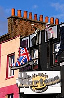 England, London, Camden. Large models of shoes hanging above a shoe shop in Camden High Street