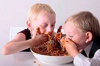 Two boys eating spaghetti