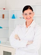 Dark_haired woman with safety glasses posing in a lab