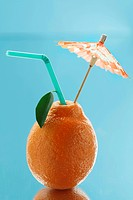 Tangerine with a straw and a cocktail umbrella