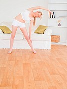 Pretty blonde female stretching in the living room in her appartment