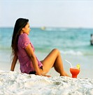 Woman with Singapore Sling on beach