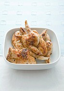 Grilled poussins in bowl, close_up