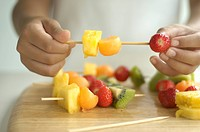 Girl making fruit kebab, close_up