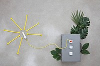 Lightbulb connected to electric sockets with leaves