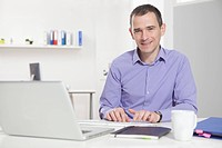 Germany, Bavaria, Munich, Businessman in office using laptop
