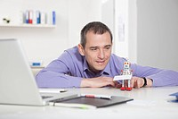 Germany, Bavaria, Munich, Businessman in office playing with roboter