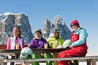 Italy, Trentino_Alto Adige, Alto Adige, Bolzano, Seiser Alm, People sitting on bench with skiing equipment and drinks