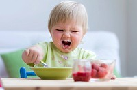 A small child making a mess with baby food