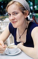 France, Mid adult woman in cafe with coffee, smiling, portrait