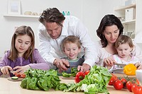 Germany, Bavaria, Munich, Mother and father helping kids to prepare salad