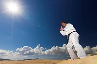 Black belt martial artist training on desert dunes