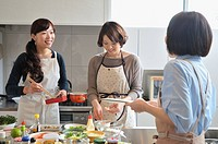 Three mid adult women cooking in the kitchen